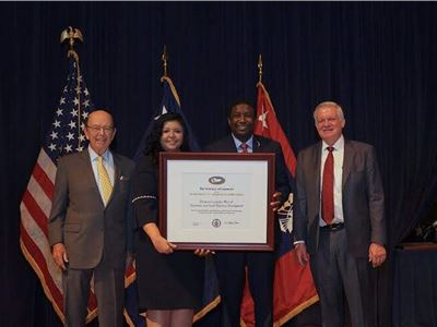 "Mayor Dale V.C. Holness and Paola Isaac Baraya Receive President's ""E"" Award for Export Service from Secretary of Commerce Wilbur Rosson."